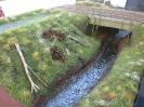 Weitere Details kommen hinzu. Sommerblumen blühen, an der Brücke wachsen Ranken aber auch ein Haufen mit Müll ist entstanden.