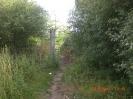 Der Pfad führt über einen kleinen Erdwall vorbei an einer Absperrung.