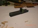 Ein Stück Vierkanntholz, die Seiten aus Pappe und die Säge integriert.